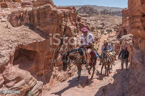 Petra, Jordan - 23.04.2018: Tourists ride on donkeys to Ad-Deir Monastery in Petra, Jordan. Travel genre photography
