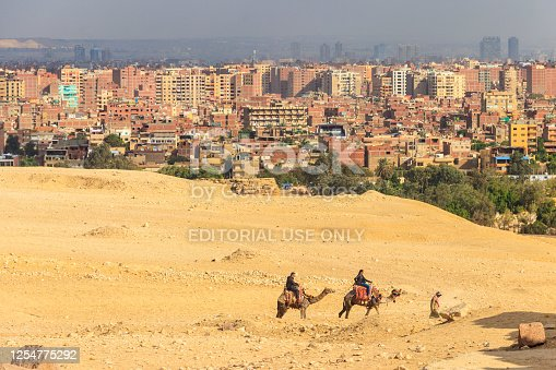 883177796 istock photo Tourists riding camels on Giza plateau against cityscape of Cairo 1254775292