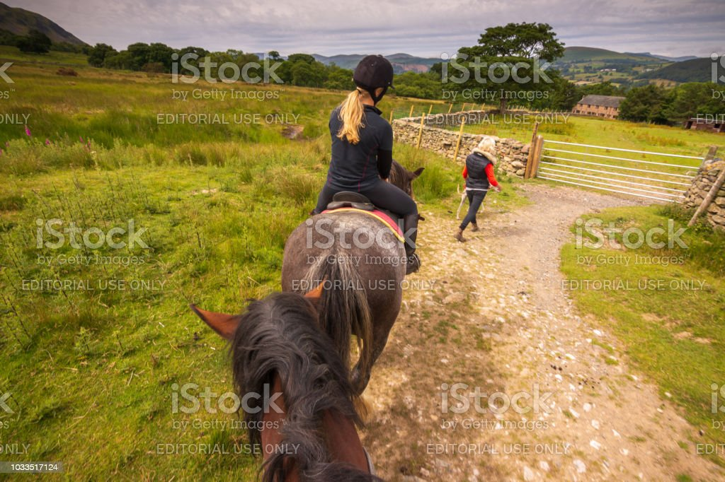 Tourists riding horses along the hills of Lake Ullswater in the English Lake District stock photo
