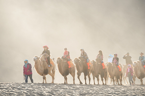 Dunhuang,China-October 13, 2015: Tourists riding the camel in the desert park