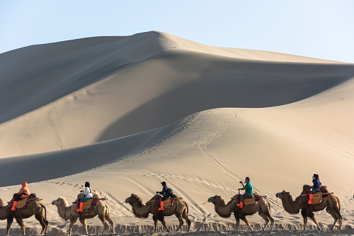 Dunhuang,China-October 13, 2015: Tourists riding the camel pass by the dunes