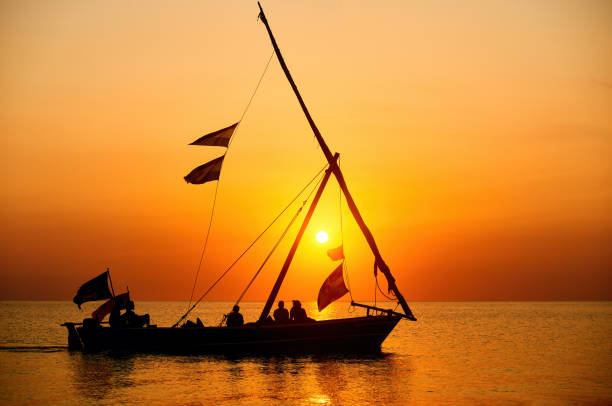 Tourists sail in a traditional boat and enjoy the colorful sunset on the island of Zanzibar,Tanzania. stock photo