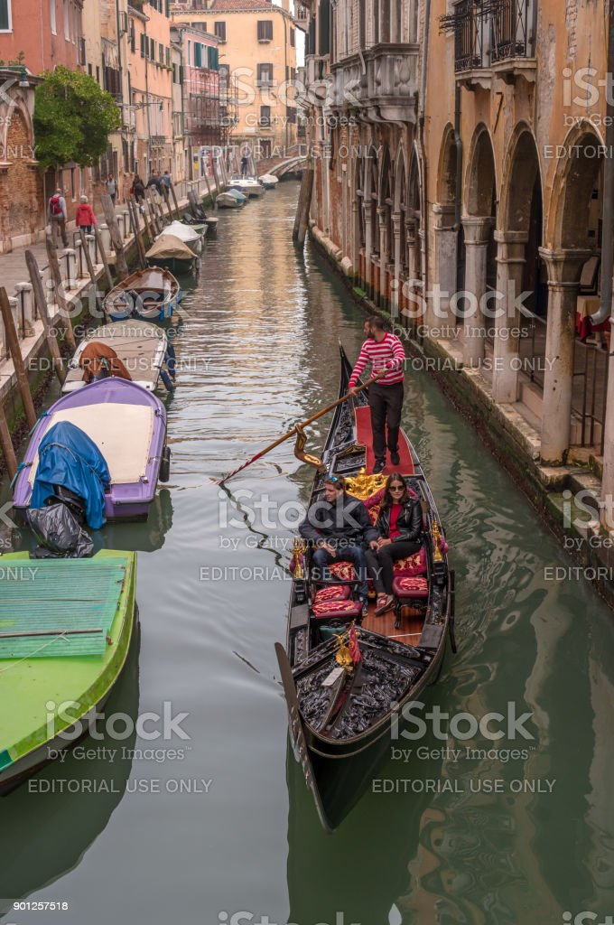 Tourists sail on a gondola on a narrow canal. The gondola is richly decorated with red carpets and gold ornaments. stock photo