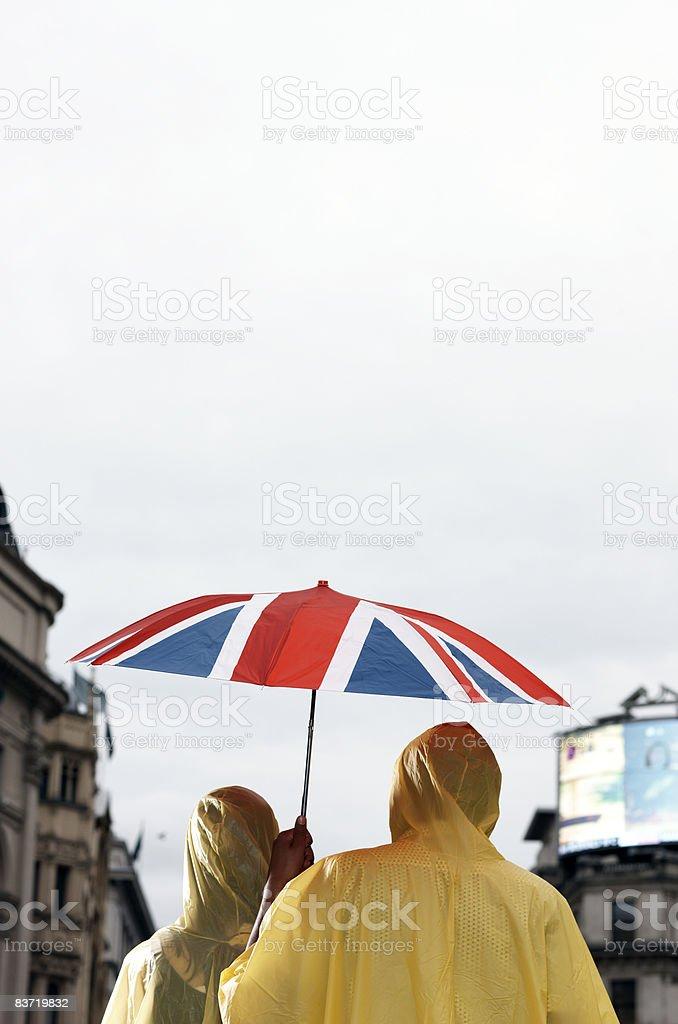 Tourists sheltering under Union Jack umbrella royalty-free stock photo