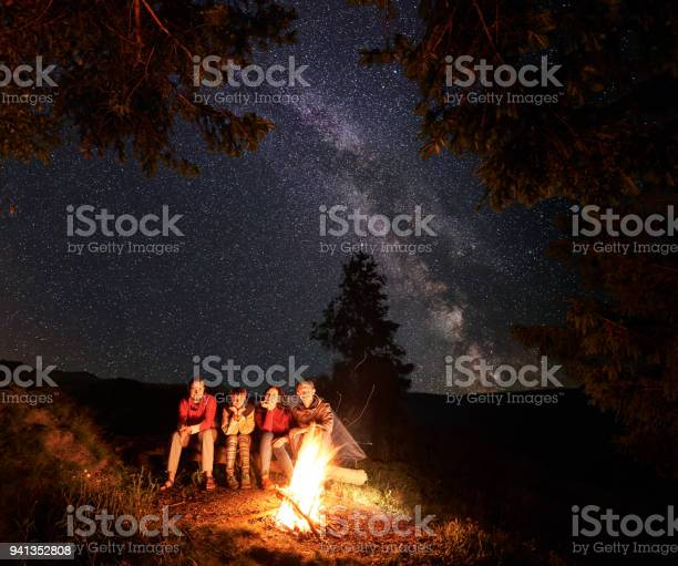 Photo of Tourists sit on log by fire under fir trees on the background of sky strewn with stars