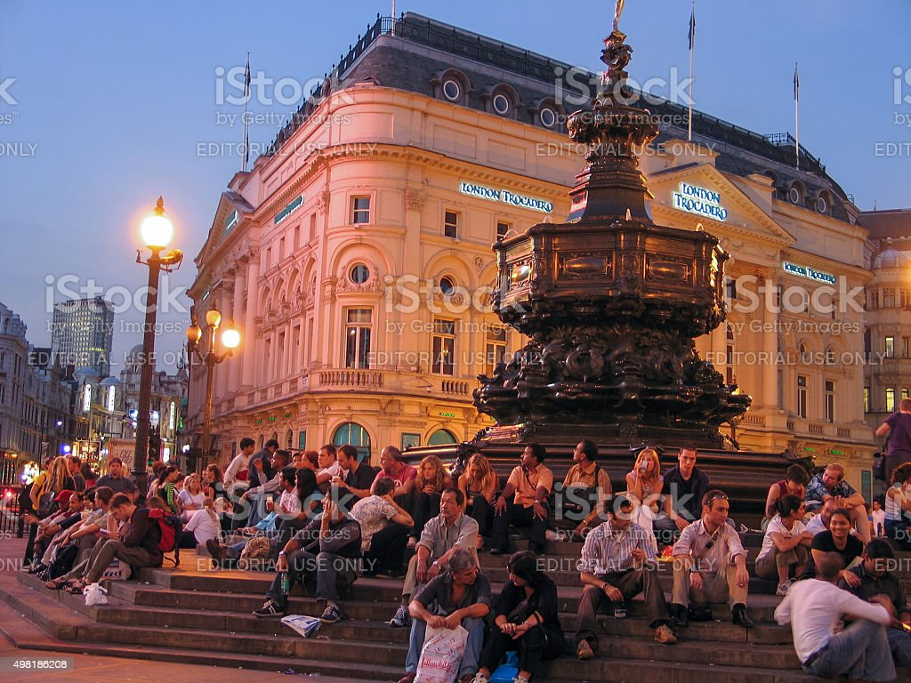 Tourists sit on the steps of Fountain in Piccadilly Circus stock photo