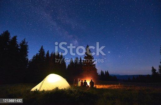 istock Tourists sitting near campfire under starry sky. 1213691432