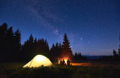 Night camping near fire, forest and mountains on background. Group of friends warming up near bright bonfire. People sitting near tourist illuminated tent under night sky full of stars and milky way.