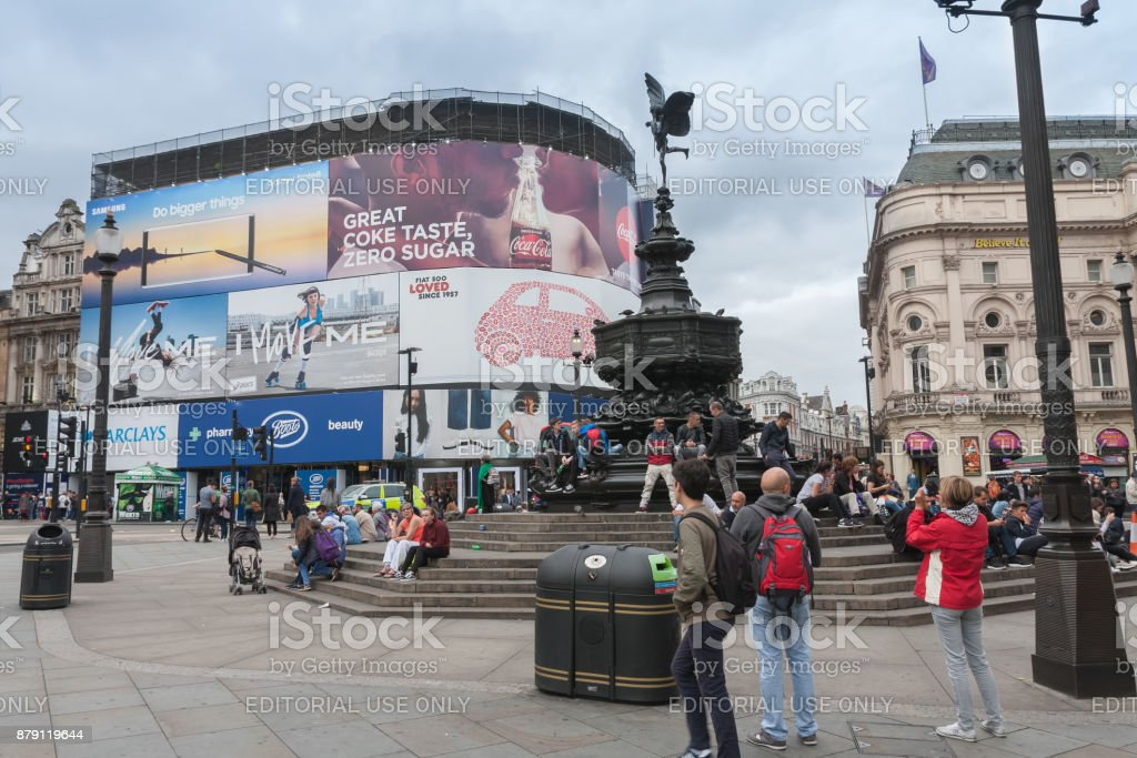 Tourists sitting on steps of the Fountain in Piccadilly Circus stock photo