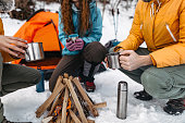 Family with coffee sitting by the campfire on snow covered landscape