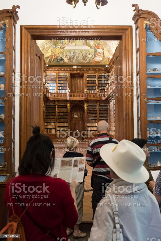 Tourists stand at the door of the library of the Strahov Monastery looking into Philosophical Hall. stock photo