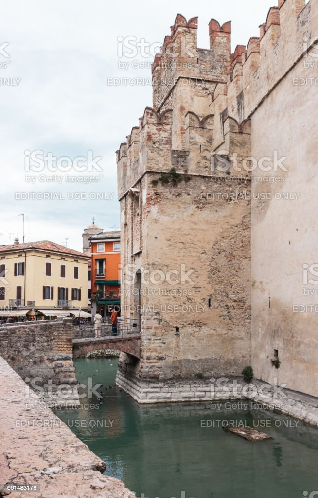 Tourists stand on bridge leading to Scaligero fortress in Sirmione stock photo