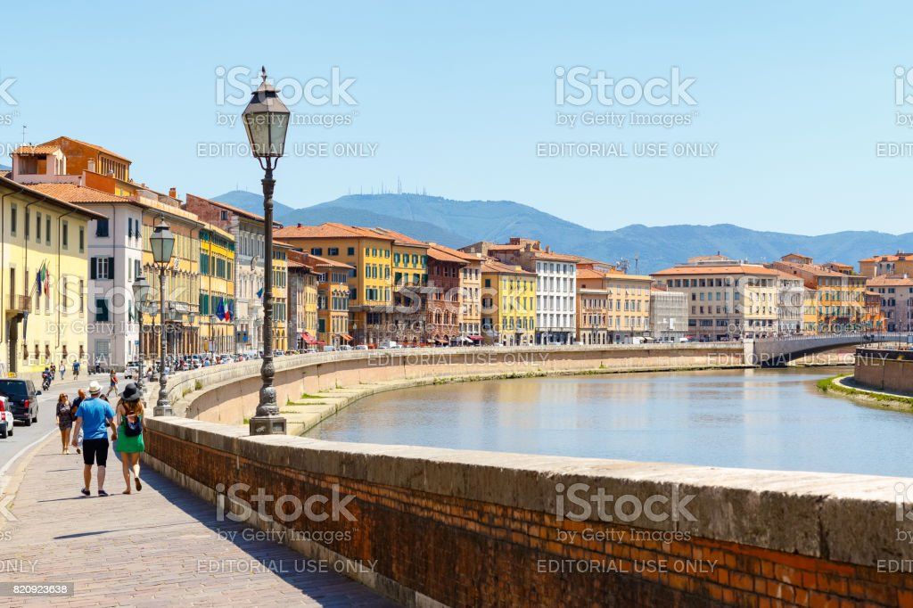 Tourists stroll along the Arno River with Pisa cityscape in the background stock photo