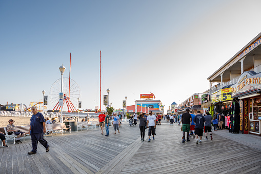 Ocean City, MD/USA - October 6, 2018: Pedestrians stroll on the boardwalk lined with shops, restaurants and tourists attractions on the East Coast beach town of Ocean City, MD in autumn