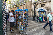 Barcelona, Spain - September 20, 2017: Tourist choosing a gift in a typical kiosk with people walking along Les Rambles in Barcelona, Catalonia, Spain