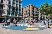 Barcelona, Spain - June 14, 2016: Many tourists strolling through Les Rambles of Barcelona where the painter Miro mosaic is on the floor.