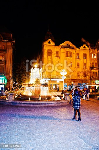 Tourists, students and locals stroll and enjoy a colourful night in front of a fountain on Piata Unirii (Union Square) in Romania