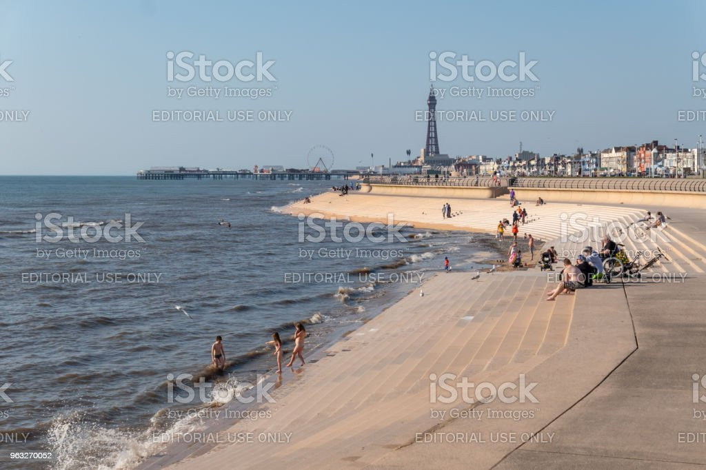 Tourists sunbath and play in the sea in Blackpool stock photo