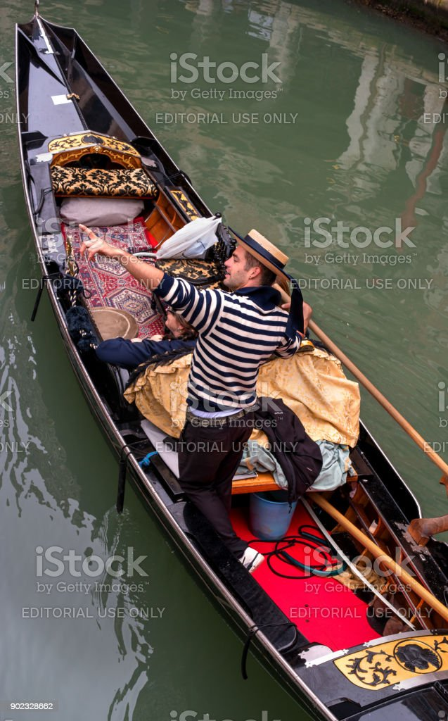 Tourists swim the gondola along a narrow canal. Gondolier points to attractions. The gondola is decorated with red carpets and gold ornaments. stock photo