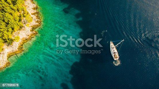 Tourists enjoy swimming by the anchored sailboat near island's coast.