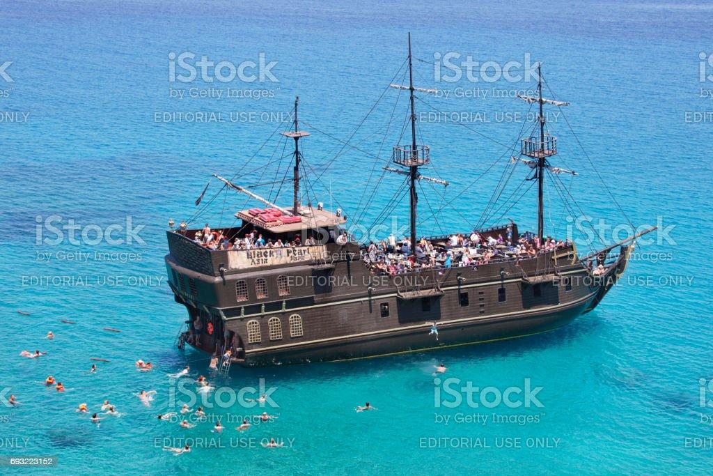 Tourists swims in the sea near the ship 'Black Pearl', Cavo Greco, Cyprus stock photo