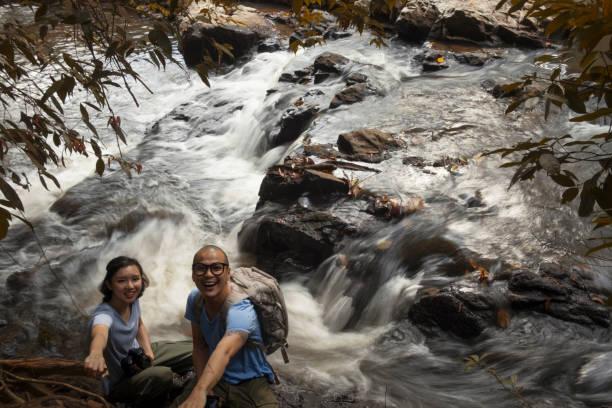 2 touristen fotografieren am wasserfall. abenteuer-reisen. - neue abenteuer stock-fotos und bilder