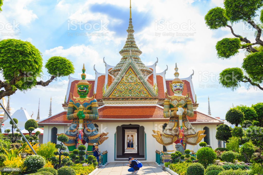 Tourists take pictures an ancient Giant statues in Wat Arun, Temple of Dawn Thailand stock photo