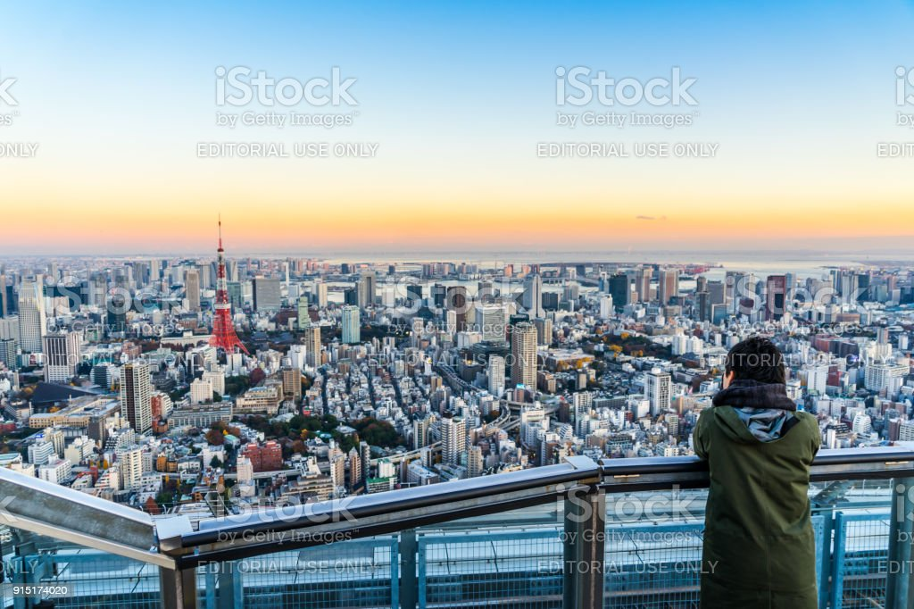 Tourists take shot of Tokyo Tower under bright golden sun and vivid twilight sky stock photo