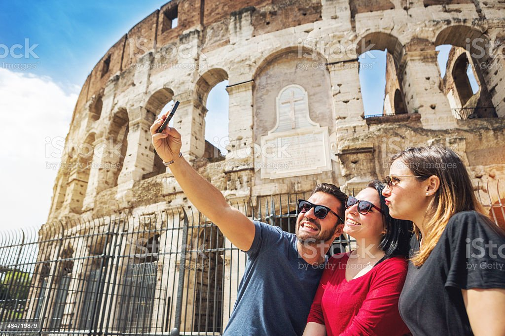 Tourists taking a selfie in front of the Coliseum, Rome royalty-free stock photo