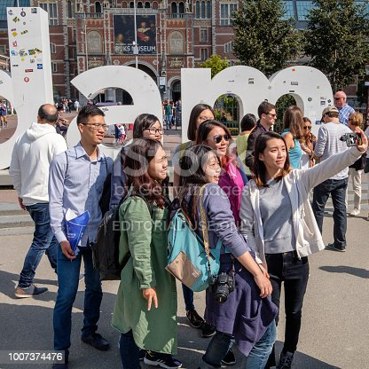 Amsterdam, Netherlands - sep 03, 2017 : Tourists taking a selfie in front of the i amsterdam sign at the museum square in Amsterdam.