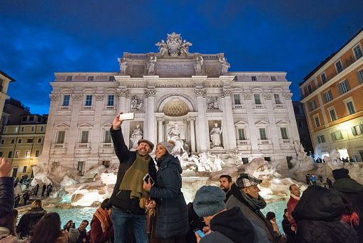 Tourists taking a selfie next to the Trevi Fountain in Rome, Italy