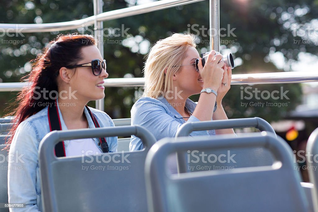 tourists taking pictures from an open top bus stock photo