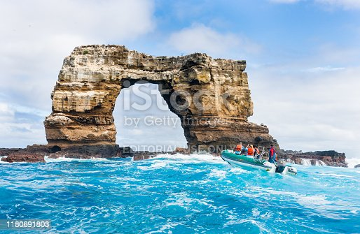 Darwin Island, Ecuador - October 4, 2019: Tourists sitting in Zodiac boat are taking pictures of Darwin Arch in Galapagos Islands.