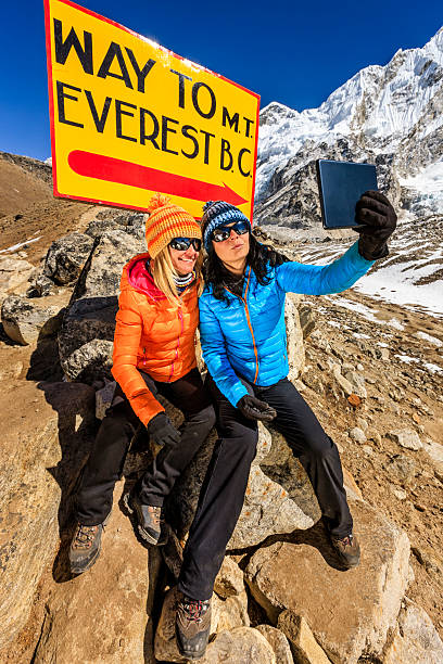 Tourists taking selfie next to signpost