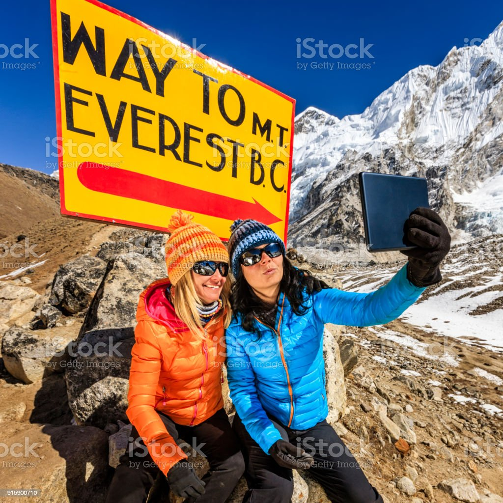 Tourists taking selfie next to signpost 'Way to MountEverest BaseCamp' stock photo