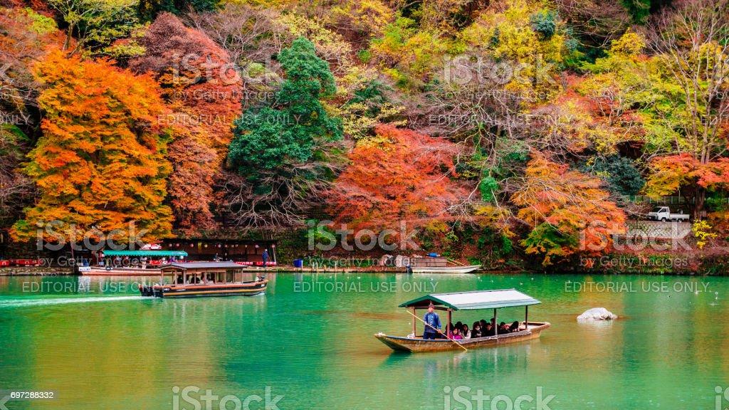 tourists to enjoy the autumn view along the bank of Katsura river in Arashiyama - foto stock