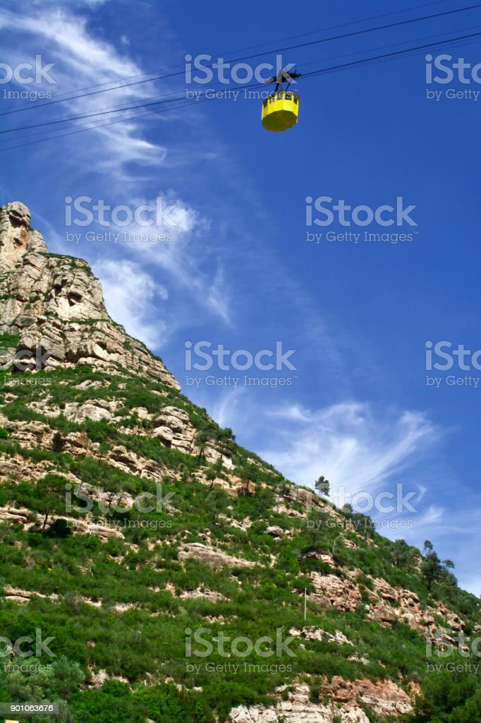 Tourists to the Abbey of Montserrat Ride the Yellow Gondolas to a Heavenly Blue Sky stock photo