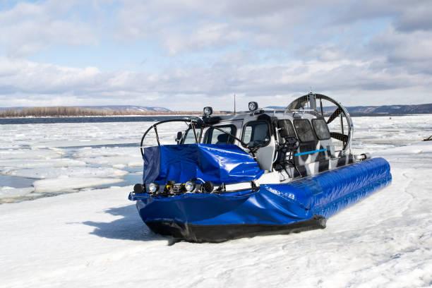 touristen reisen auf dem eis eines gefrorenen flusses auf booten auf luftkissen. - rettungsinsel stock-fotos und bilder