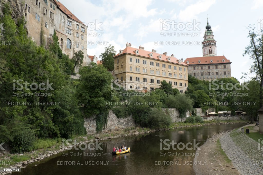 Tourists traveling down the Vltava River on yellow raft, the famous Castle Tower and Castle in the background. stock photo
