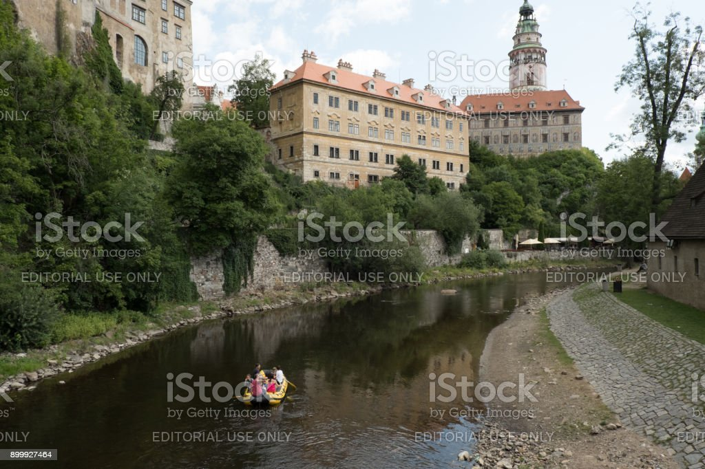 Tourists traveling down the Vltava River on yellow raft, the famous Castle Tower and Cesky Krumlov Castle in the background on a summer day. stock photo