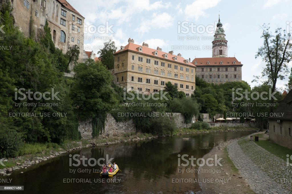 Tourists traveling down the Vltava River on yellow raft, the famous Castle Tower in the background. stock photo