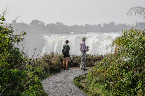Tourists viewing the falls at Victoria Falls Zimbabwe Victoria Falls, Zimbabwe, 19 September 2018. Two tourists at the Victoria Falls in Zimbabwe look across the gorge that receives millions of tons of water from the River Zambesi over the Victoria Falls in Zimbabwe. The waterfalls are divided between Zimbabwe and Zambia, with most of them being on the Zimbabwe side. whiteway stock pictures, royalty-free photos & images