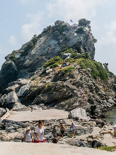 tourists visit a remote chapel on the island of skopelos - mamma mia stock photos and pictures