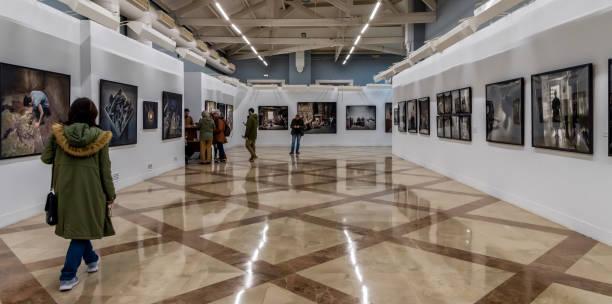 tourists visit an art collection in downtown huelva, spain during 2018 latitudes international photography festival; panoramic view. - museu imagens e fotografias de stock