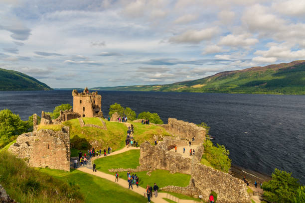 Tourists visit Urquhart's Scottish Castle Inverness, Scotland  - August 10, 2017: View of Urquhart Castle in Scotland with a row of visitors exploring castle ruins. inverness scotland stock pictures, royalty-free photos & images