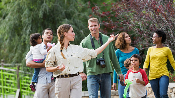 tourists visiting a park - guide stockfoto's en -beelden