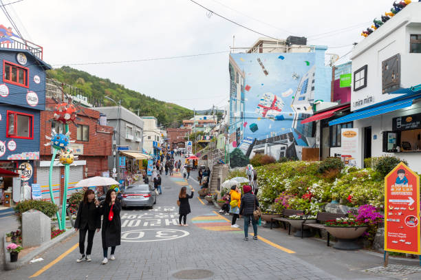 Tourists visiting Gamcheon Culture Village, famous attraction with vibrantly painted houses decorated with murals and sculptures on hillside of coastal mountain in Busan, South Korea stock photo