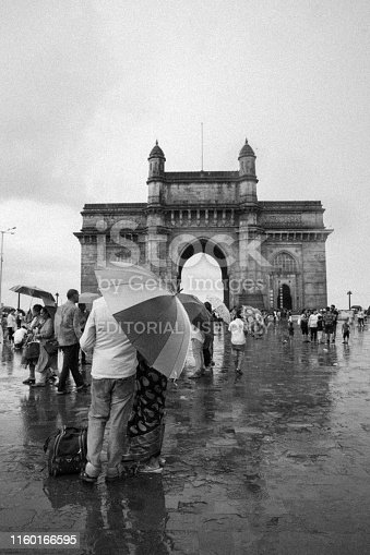 On a Rainy Day, Tourists Visiting the Gateway of India, Mumbai. The Gateway of India is a monument built during the 20th century. Gateway of India was build to commemorate the arrival of Queen Empress Mary & King Emperor George V at Apollo Bunder for their visit to India in 1911.