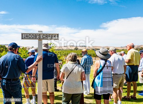 Tourists visiting Jacobs creek vineyard in Barossa valley Australia. A group of tourists, men and women are seen from behind when they watch the growing wine under a blue sky. A SIGN SAYS JACOBS CREEK.