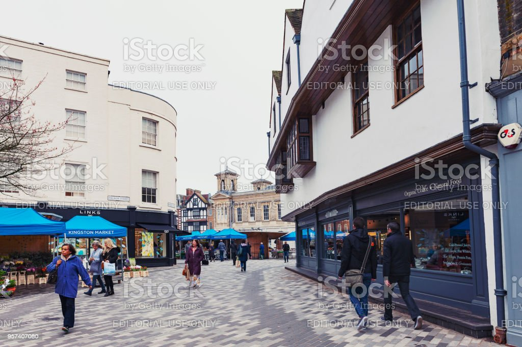 Tourists visiting Kingston Market Place, town centre with lots of shops and stores in old buildings stock photo